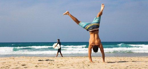Mann macht Handstand am Strand