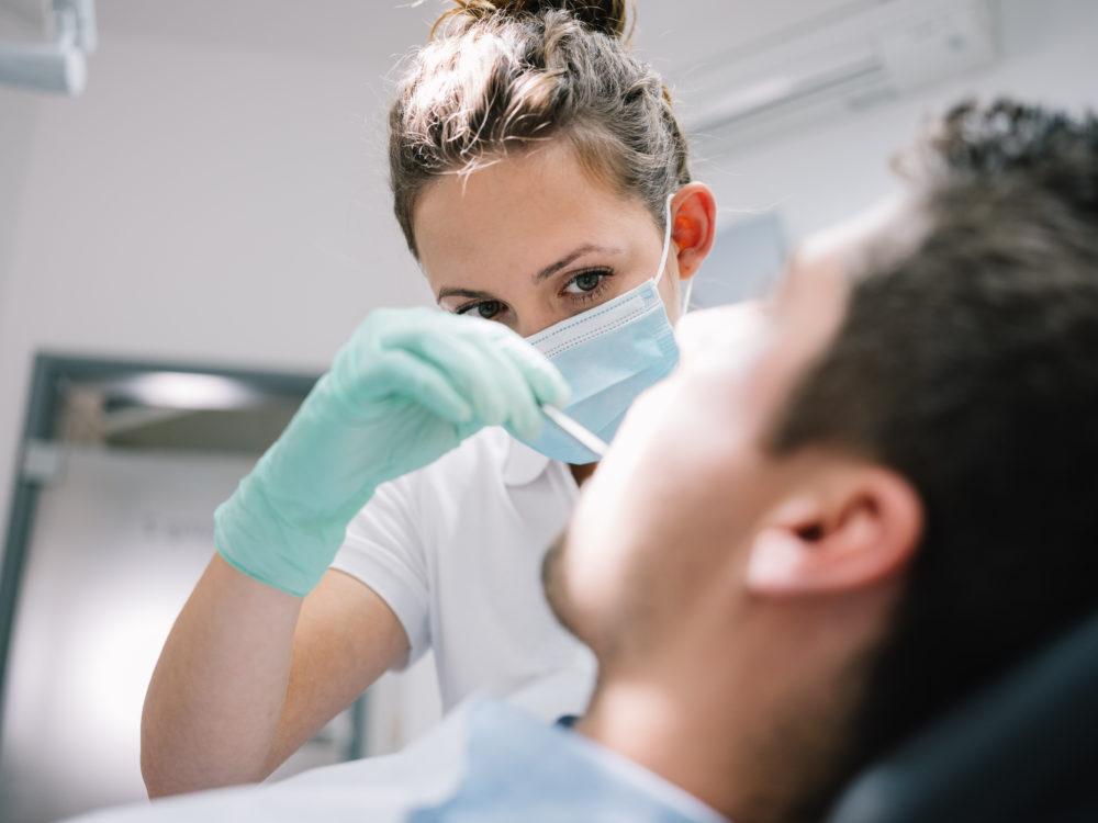 Zahnaerztin schaut in mund scaled - Implantate - der moderne, nachhaltige Zahnersatz